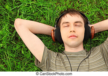 teenager lies on grass in headphones - young man lies on...
