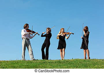 four musicians play violins against sky, focus on left man