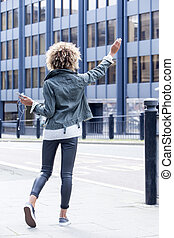 I need a taxi! - Young woman signalling for a taxi in the...