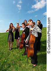 Group of violinists play standing on grass