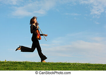 girl with violin runs on grass against  sky, side view