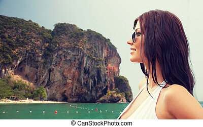 smiling young woman with sunglasses on beach - summer...