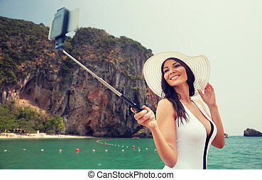 happy woman taking selfie with smartphone on beach - travel,...