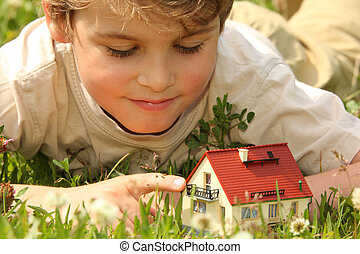 boy and house model in grass