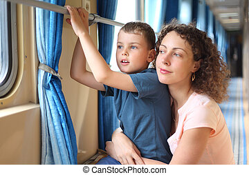 mother and son in train`s corridor looks in window