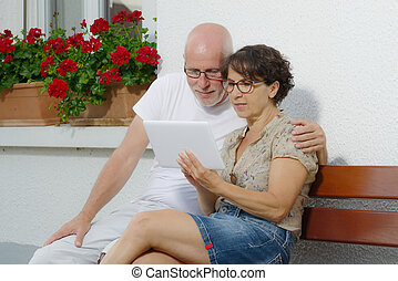 senior couple with a tablet, outside - a senior couple with...