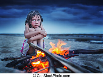 Little girl is heated by the fire. - Desperate child hugging...