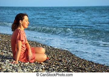 young woman sits ashore of sea
