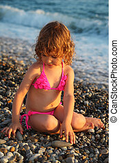 little girl sits on beach