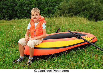 boy sits on an inflatable boat on lawn