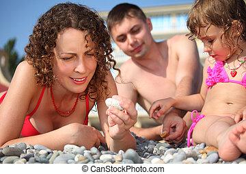 family on pebble in swimwear