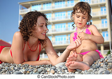Mother with daughter on pebble in swimwear