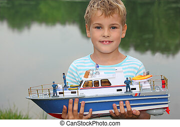 boy with toy ship in hands ashore