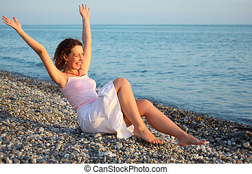 young woman sits ashore of sea with rised hands