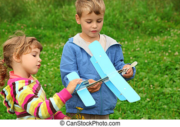 little girl and boy with toy airplane in hands outdoor