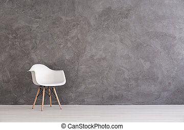 Interplay of different textures - White plastic chair on a...