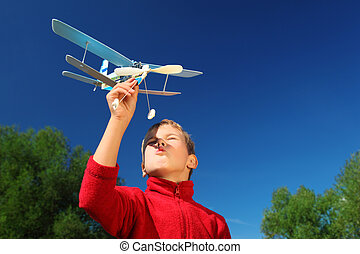 boy with toy airplane in hands outdoor against sky