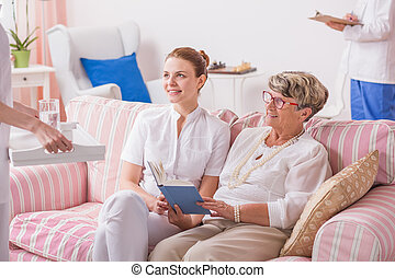 Treatment in professional clinic - Elder woman with nurse...