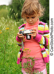 little girl with photo camera outdoor
