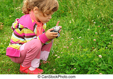 little girl with photo camera outdoor, looking on screen