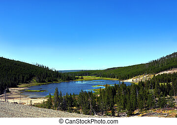 Exploring Yellowstone - Blue skies are reflected on the...