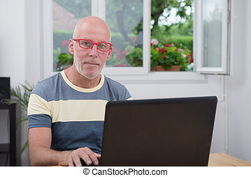 mature man with laptop in his home