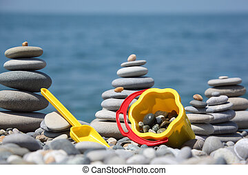 Yellow children\'s bucket with scoop and stone stacks on...