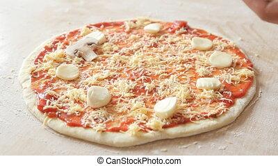 Chef adding champignons on pizza dough