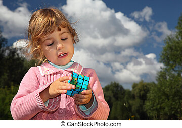 little girl with magic cube outdoor in summer