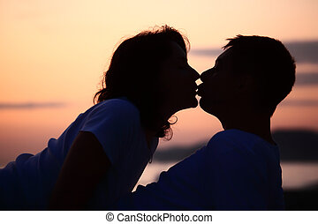silhouette kissing man and woman on beach
