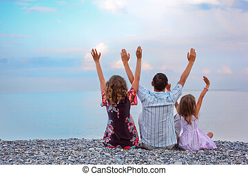 Happy family with little girl sitting on stony beach lifted...