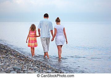 Happy family with little girl walk on beach in evening