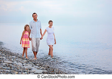 Happy family with little girl walk on beach in evening, focus on mother