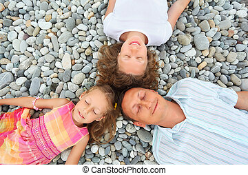 Happy family with little girl lying on stony beach, closed...