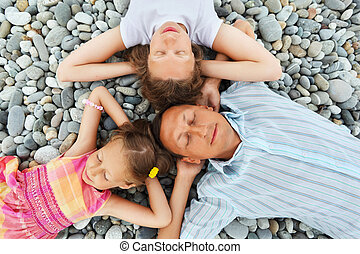 Happy family with little girl lying on stony beach,...