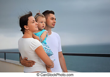 young man and beautiful woman protects little girl from wind...