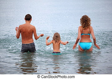 Happy family with little girl splashes water hands standing on belt in sea, standing back