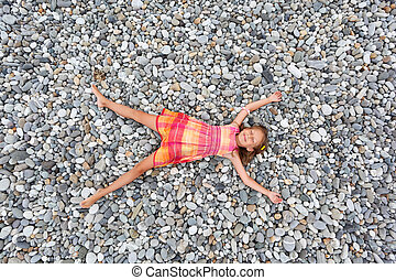 little girl lying on stones on stone seacoast