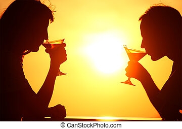 Female and man\'s silhouettes on sunset  drink from glasses