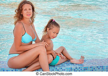 beautiful woman with little girl sit near in pool