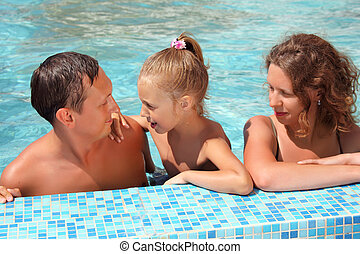 Happy family with little girl bathe in pool