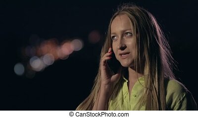 Smiling woman talking on phone at night city