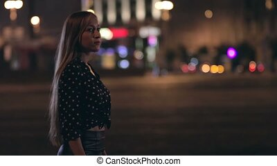 Young woman walking through a night city street - Young...