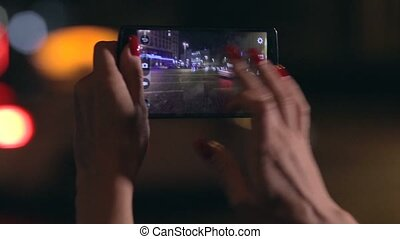Woman takes photo of city in streetlights at night - Close...
