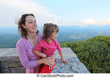 mother and daughter look on mountain from balcony