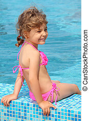 little girl sits on border of pool