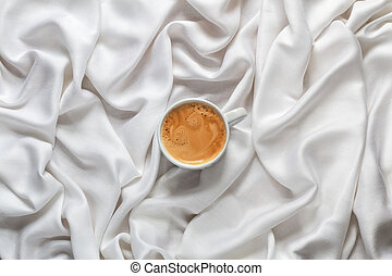 Coffee cup on a white silk fabric. Espresso with froth in the form of smiley face. Top view.