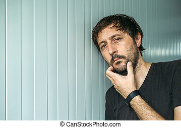 Pensive adult unshaven man with hand on chin