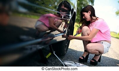 Attractive girl trying to remove wheel with wrench -...