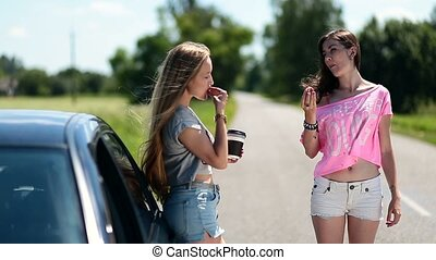 Young women eating and drinking coffee near car - Young...
